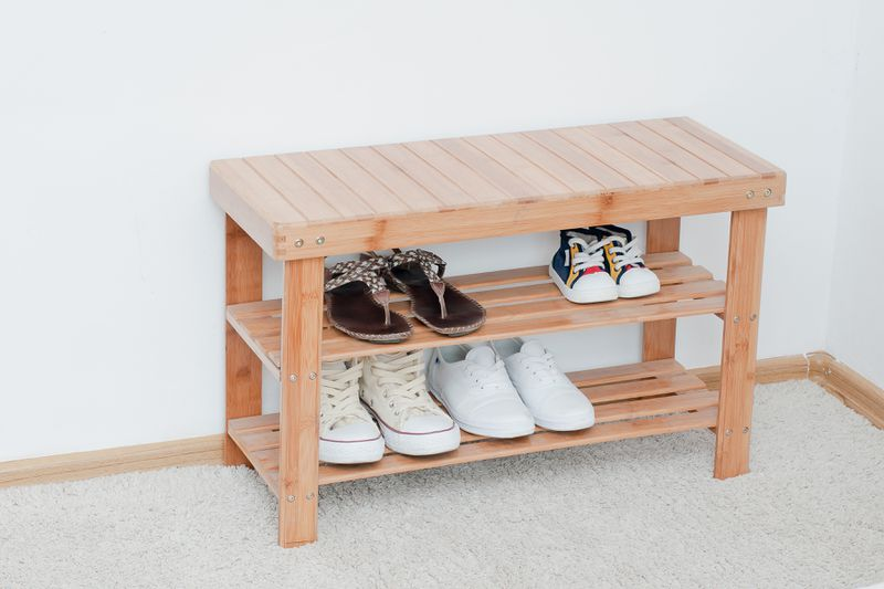 A small wooden entry bench holding two rows of shoes.