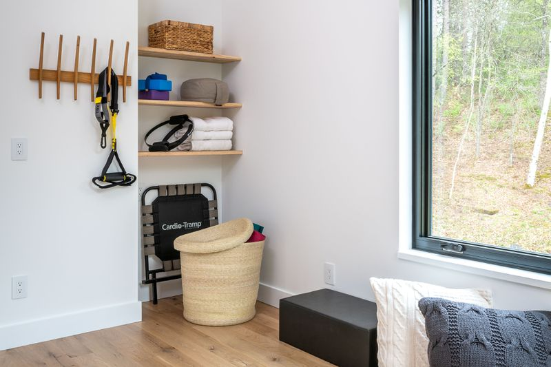 A woven hamper sits in the corner of a workout room.