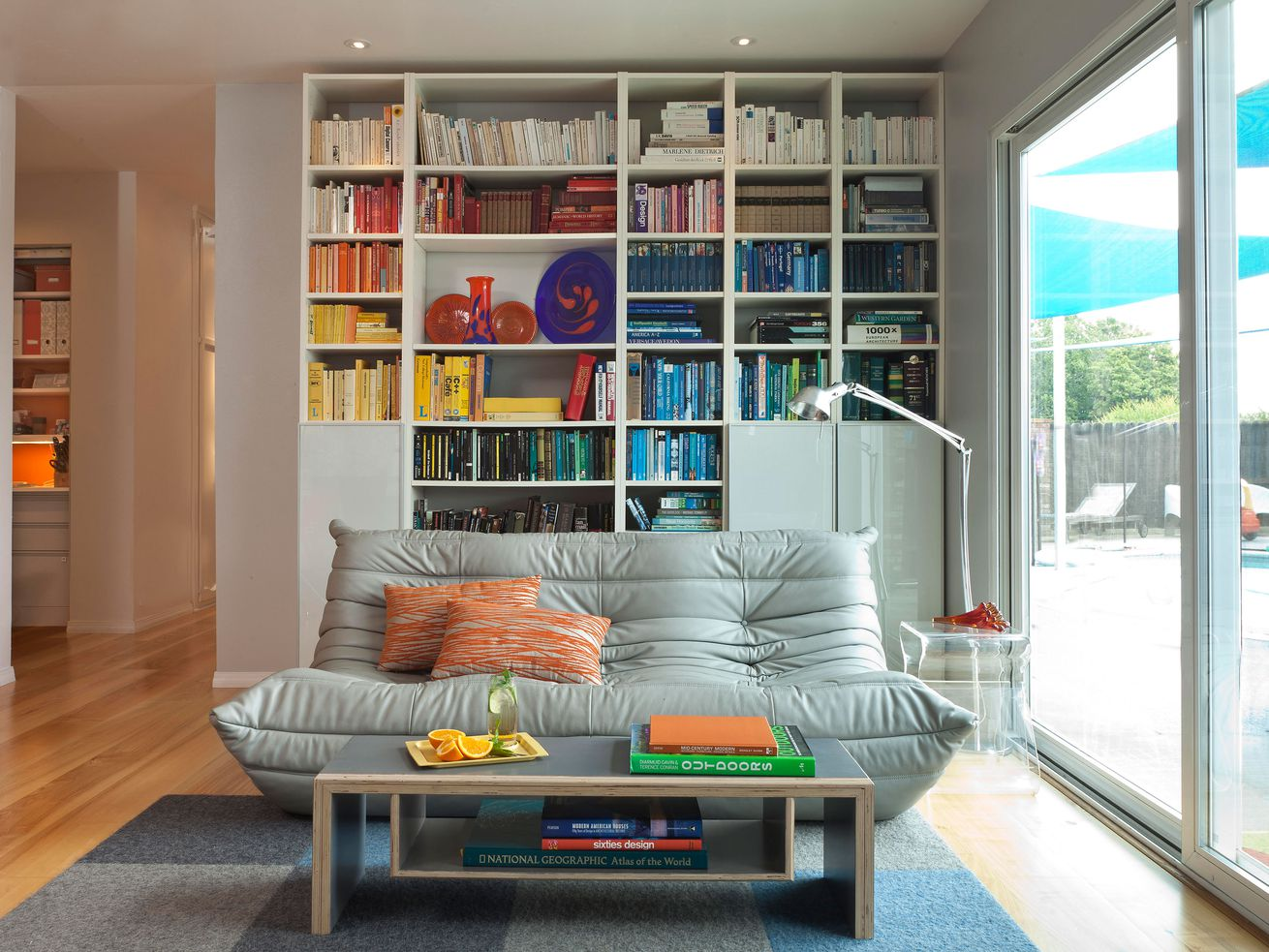 A modern living room with a library full of books that are color coordinated in a rainbow spectrum.