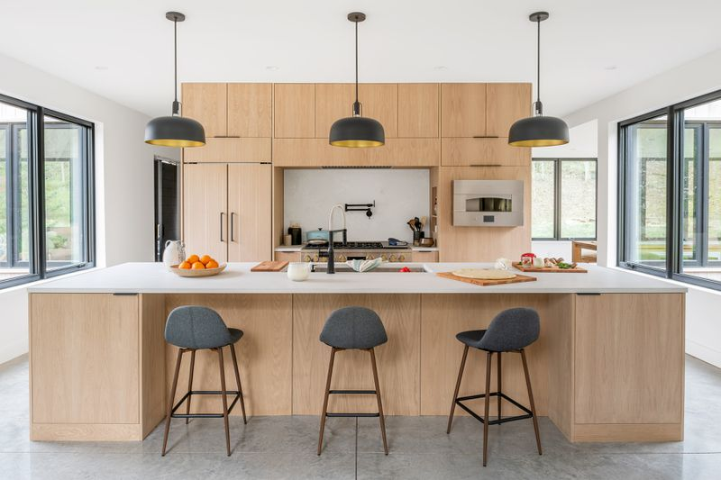 Breakfast bar in the Modern Barnhouse. Pendant lights align over the three chairs at the island.
