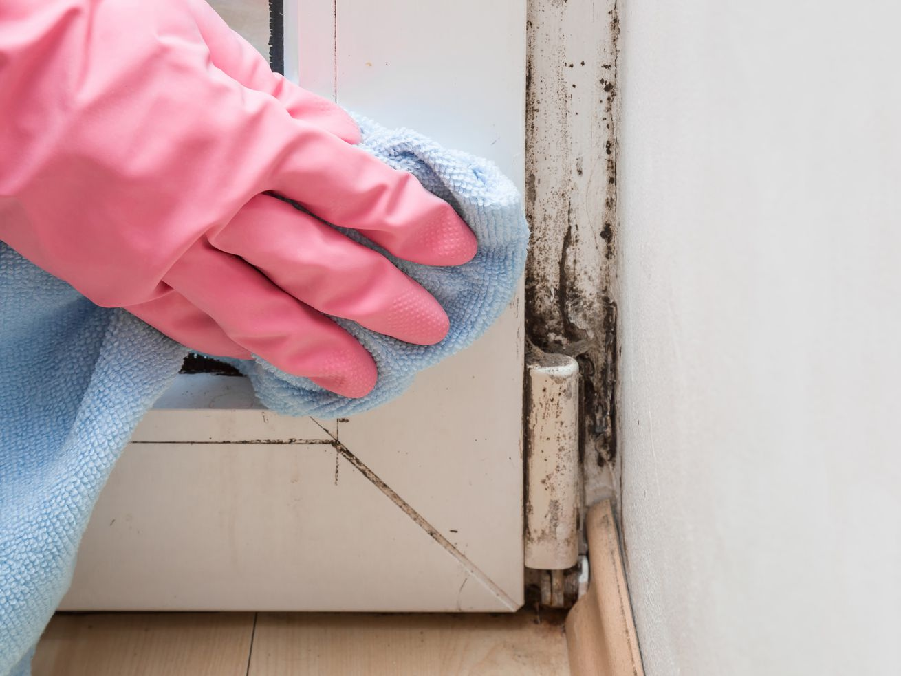 A hand wearing a pink cleaning glove removing mold from the corner of a door.