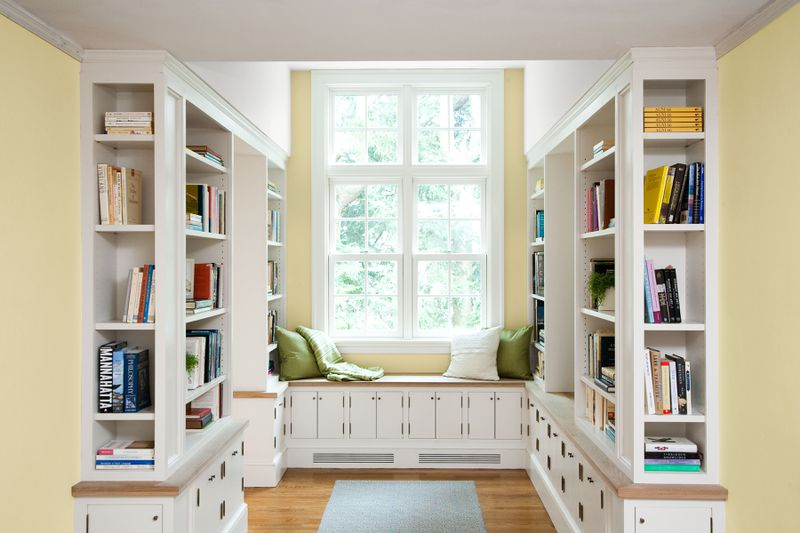 A home library with a large window as the focal point.