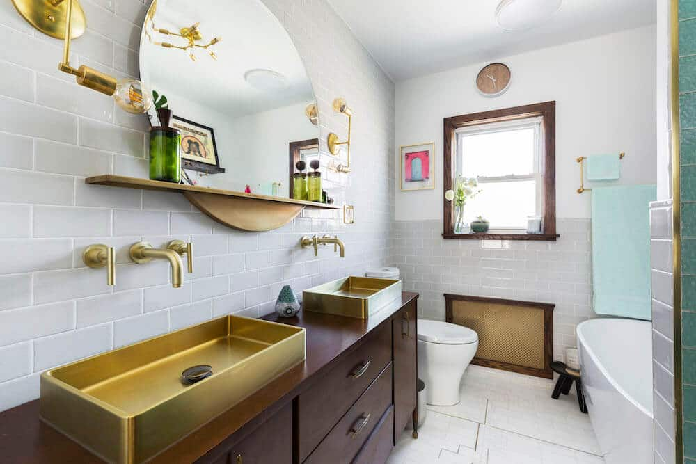 Image of a bathroom with white subway tile and gold accents