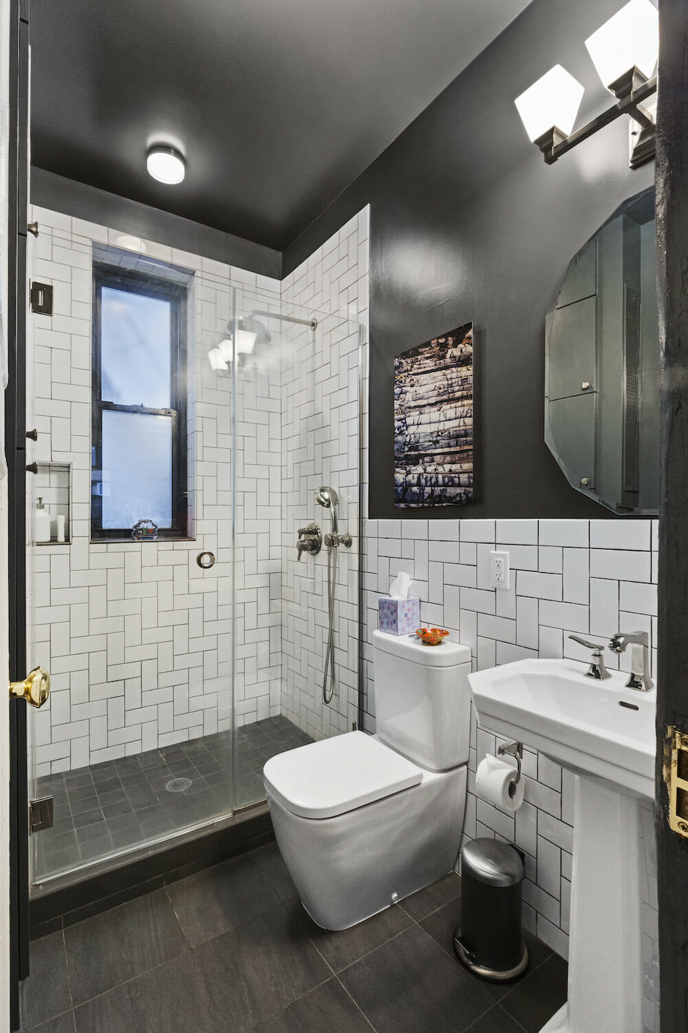 Image of a bathroom with white subway tile in a herringbone pattern