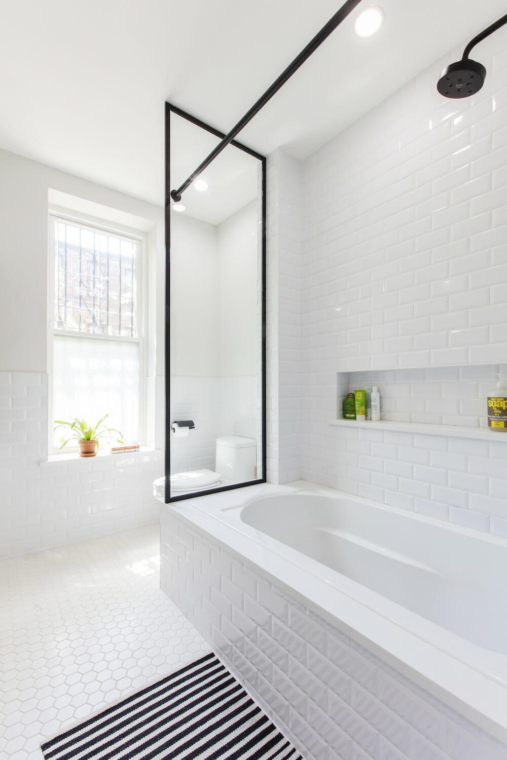 Image of a renovated bathroom with white subway tile and bathtub
