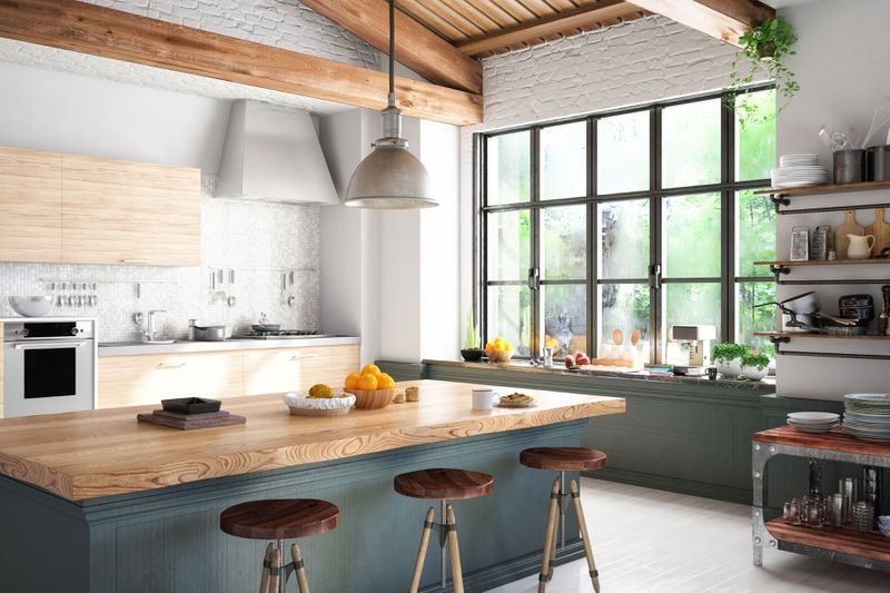 A kitchen with wooden touches in the beams, cabinets, kitchen island and stools.