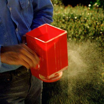 Person putting fertilizer on plants.
