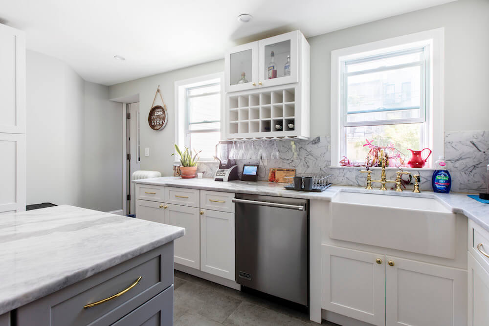 Kitchen with tile floor, gray kitchen island, white cabinets and gold cabinet pulls