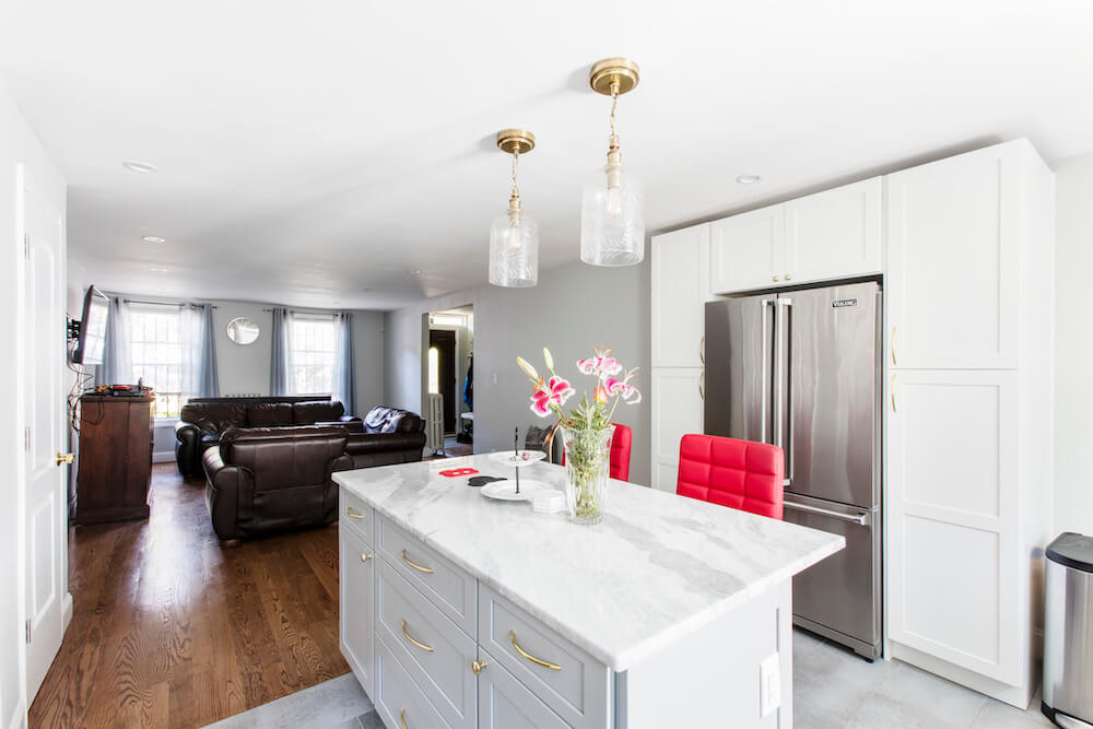 Open concept kitchen looking into living room with hardwood floors and recessed lighting