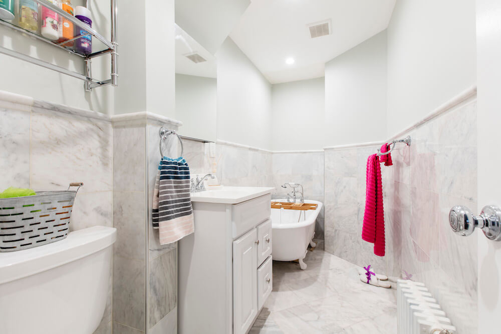 Remodeled bathroom with soaking bathtub, gray-white tile floors, and a white bathroom vanity