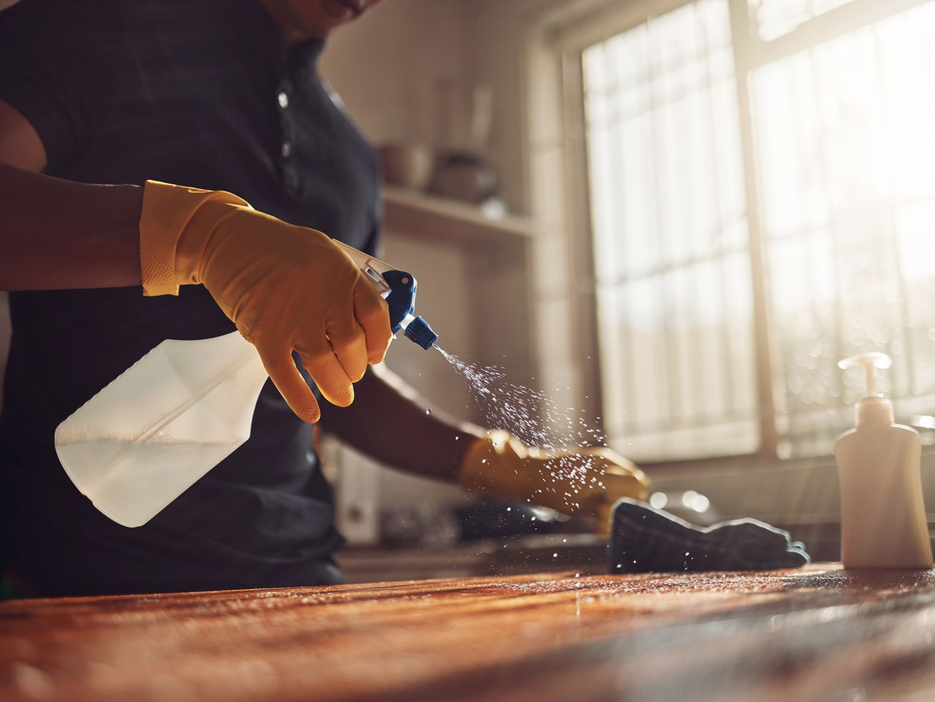 A woman cleans a butcher block countertop with a spray bottle and gloves.