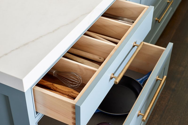 A detailed shot of open drawers. The top drawer has dividers for large cooking utensils and the bottom drawer holds pots and pans.