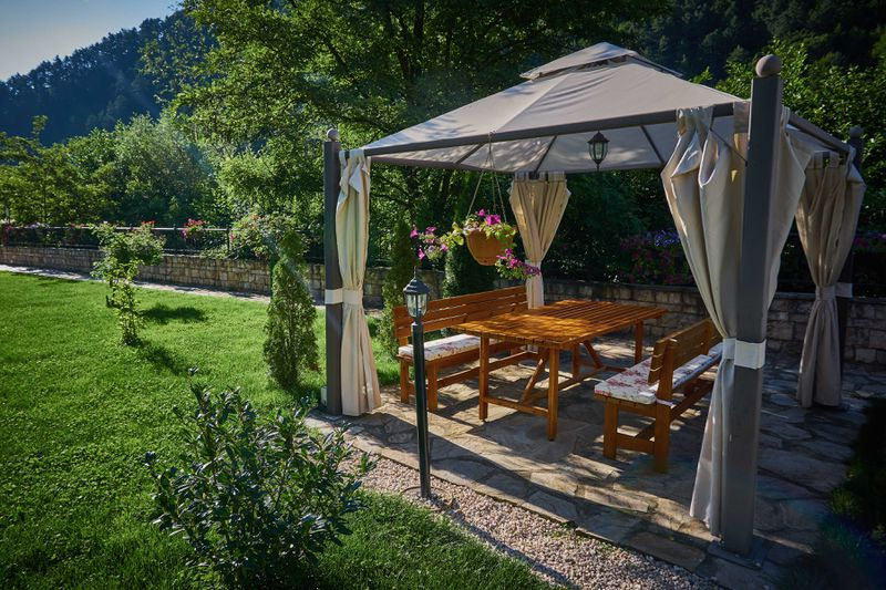 A fabric gazebo stands along in a backyard, equipped with lighting, curtains and a table.