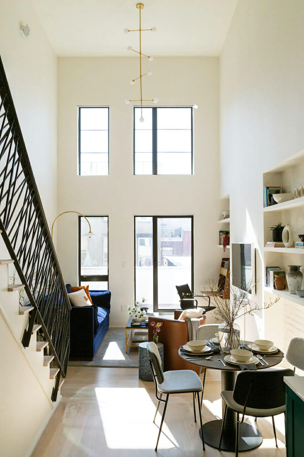 Living room with double height loft ceilings and gold lighting fixture