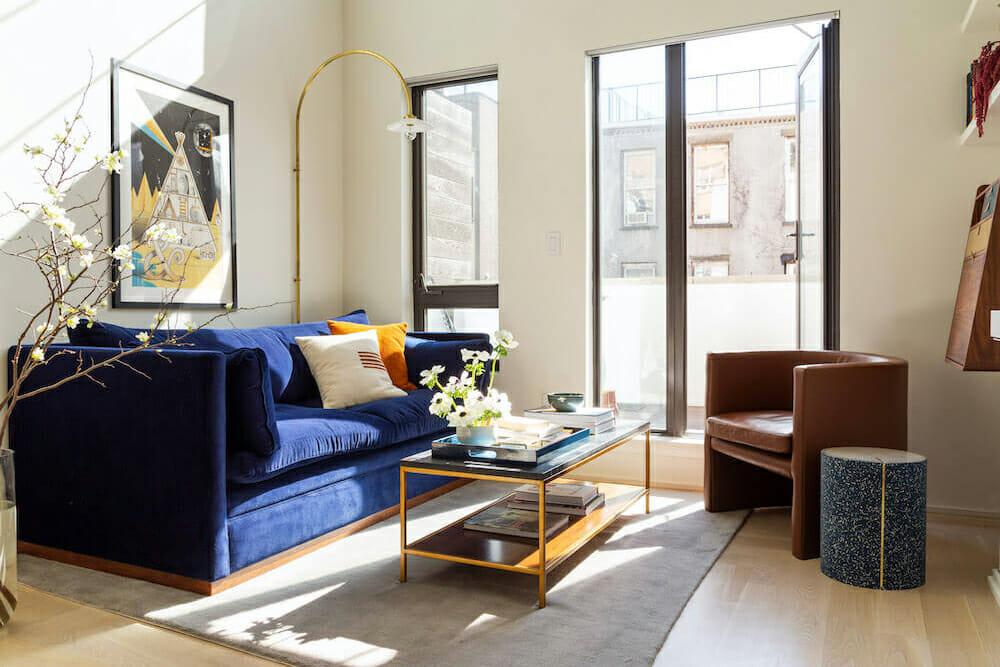 A modern Williamsburg loft living room with blue velvet couch