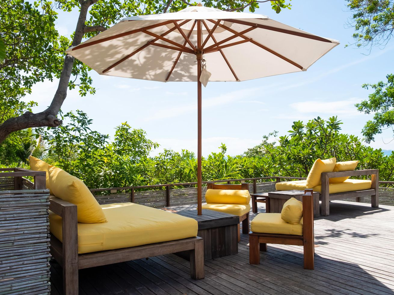 An outdoor seating area with a large white umbrella casting shade.