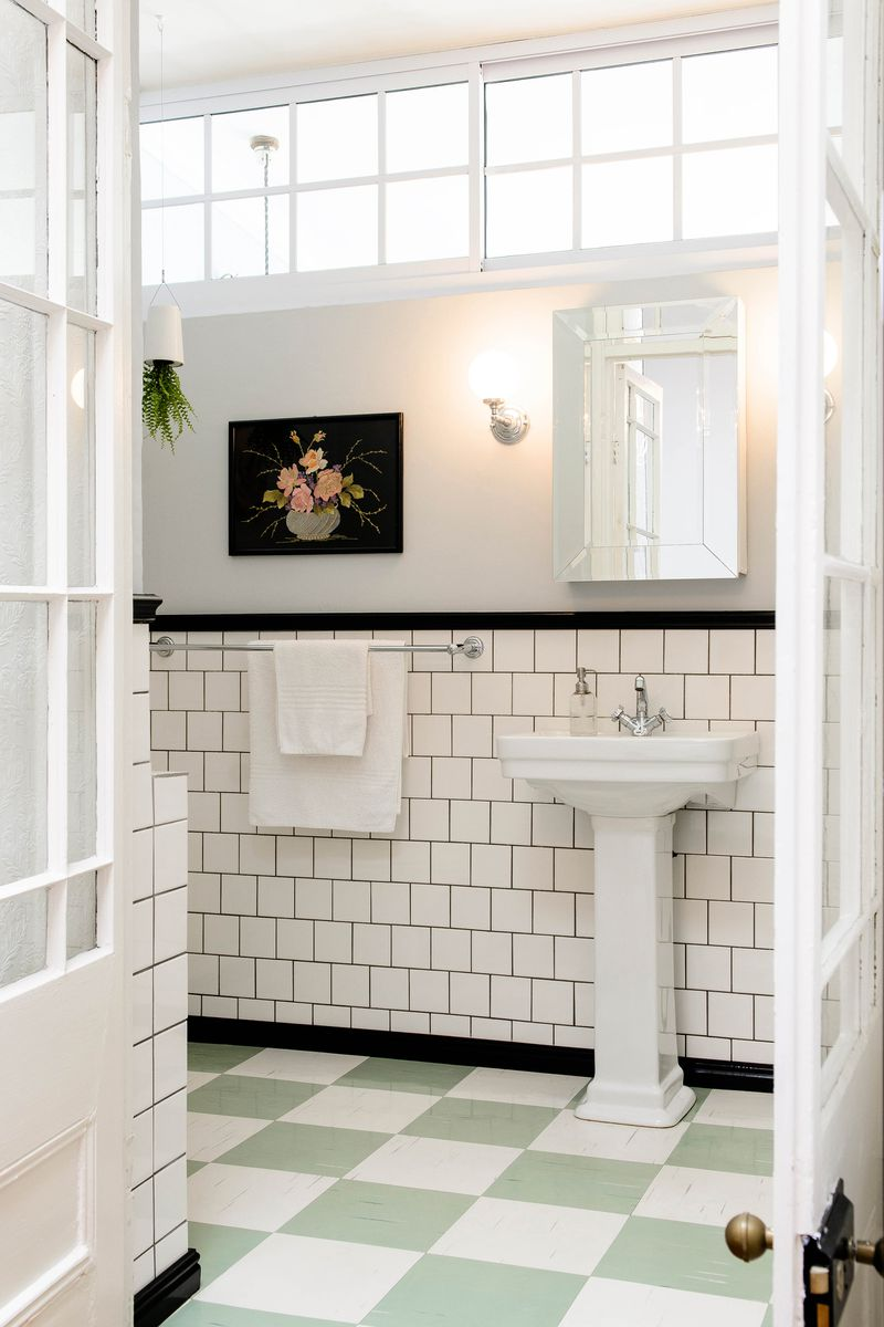 A bathroom with green and white block linoleum tiles.