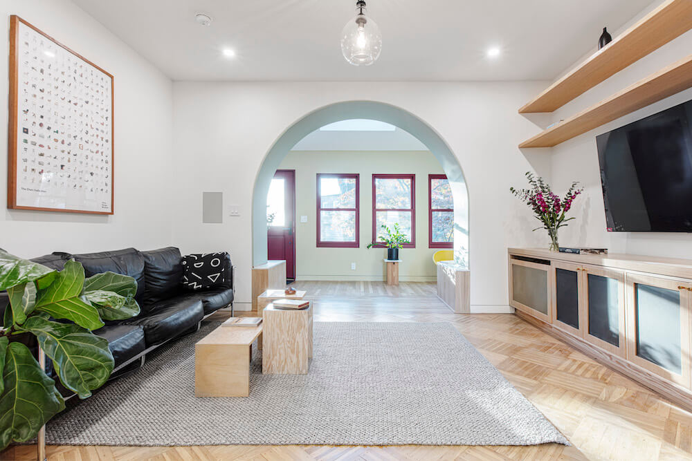 Modern living room with pale hardwood floors, open shelves and arched entryway