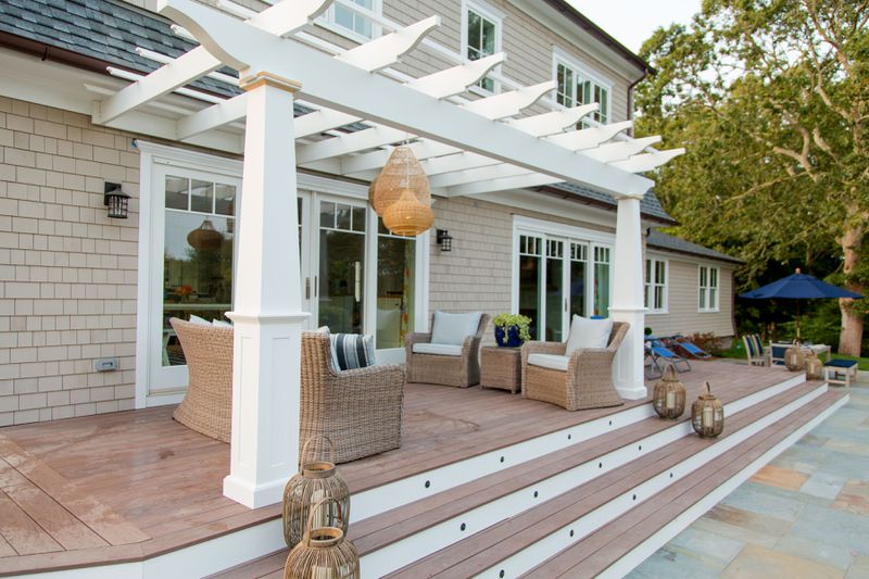 The backyard of the Westerly house with a deck and seating area under a pergola.