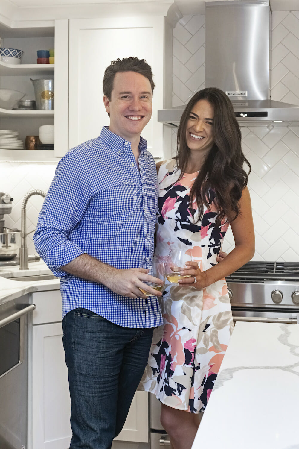 Husband and wife standing in newly renovated kitchen with quartz countertops
