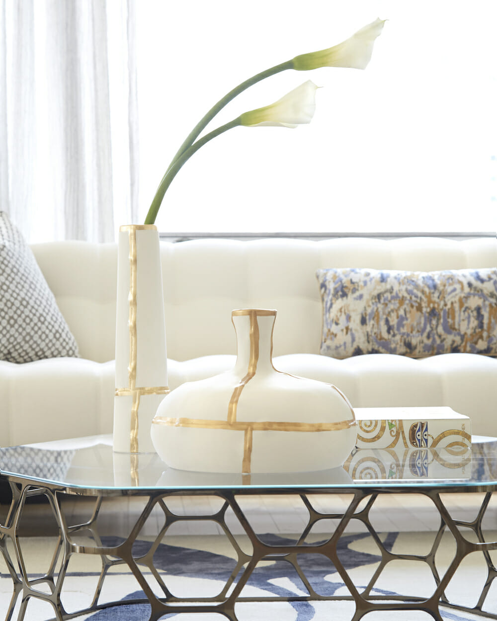 Closeup of modern living room coffee table with flower vase and modern white sofa