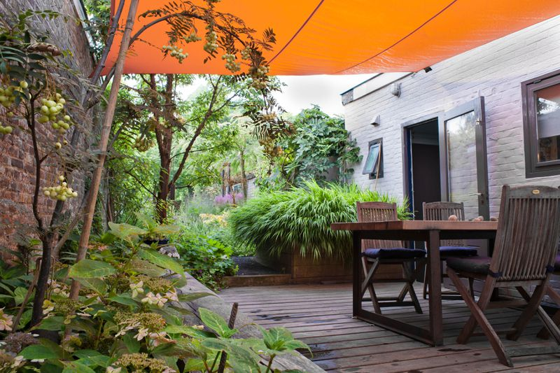 An outdoor seating area with an orange tarp overhead for shade.