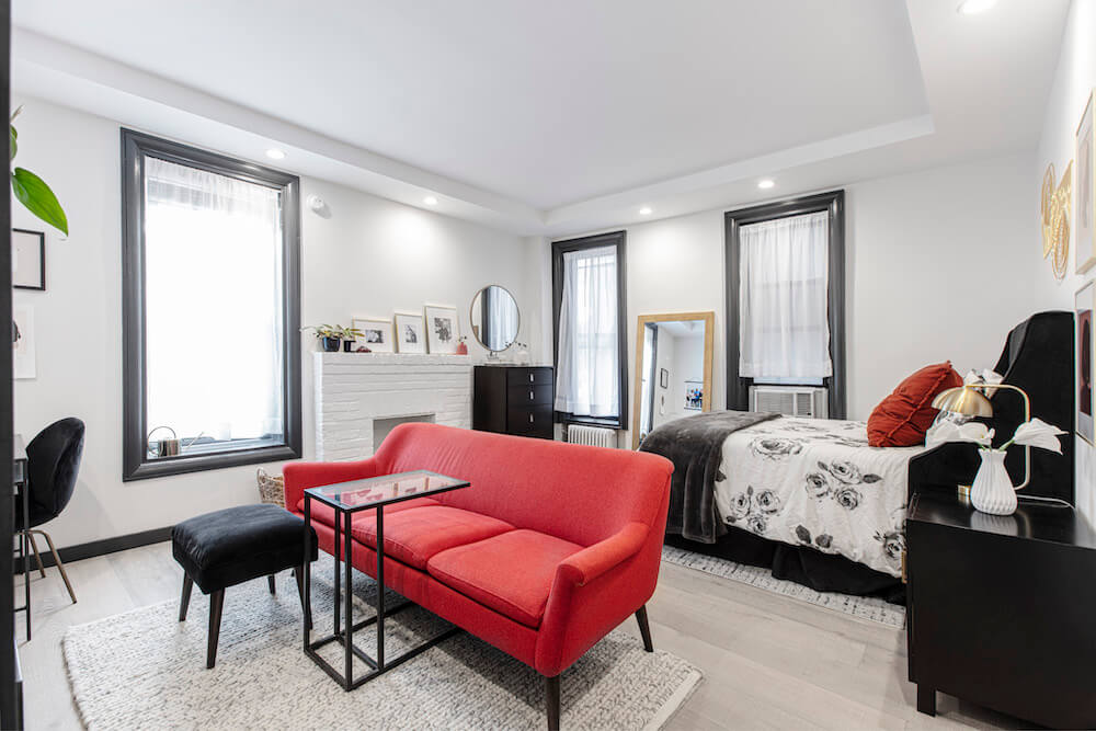 Modern living room in studio apartment with bold red sofa and black accents