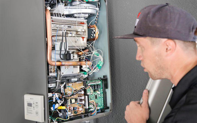 Man Looks Inside Tankless Water Heater