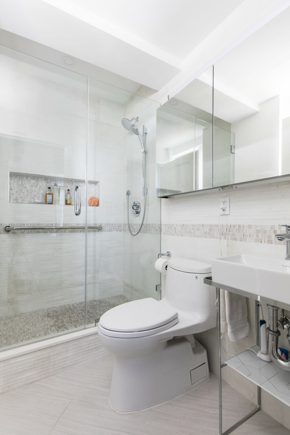 A remodeled bathroom with step-in shower, glass door and shower niche storage