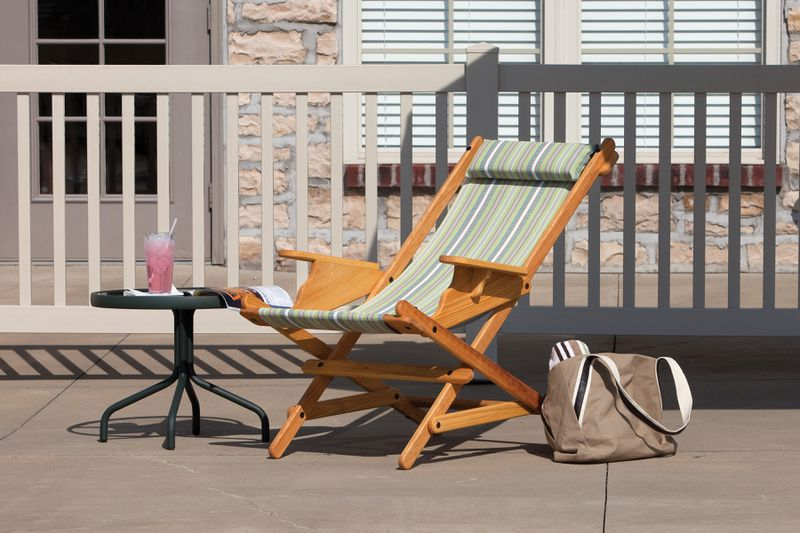 A handmade sling chair sits on a pool deck.