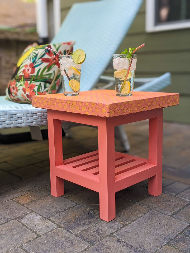 A coral colored side table with a patterned patio paver on top.